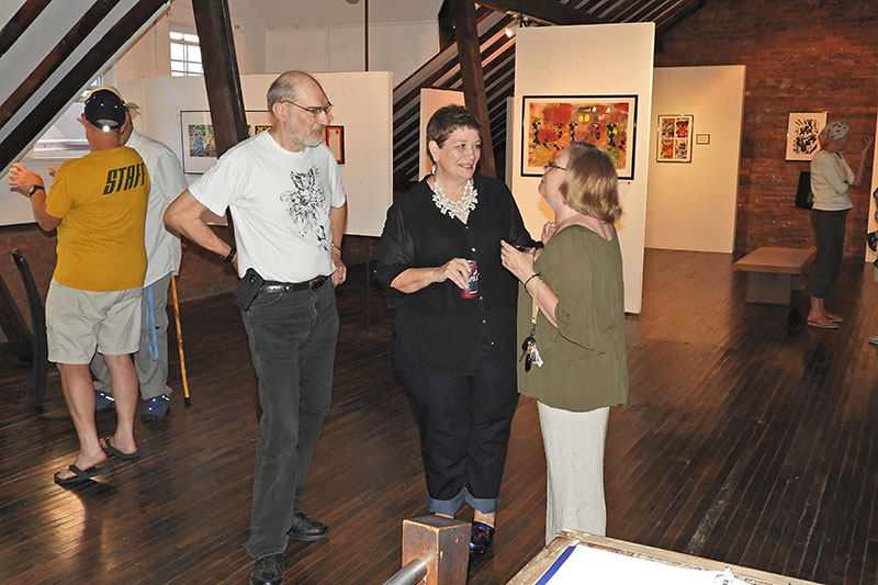 UNY Oswego graduate student Suzanne Beason (center) and her husband, Kirk (left), speak with visitors