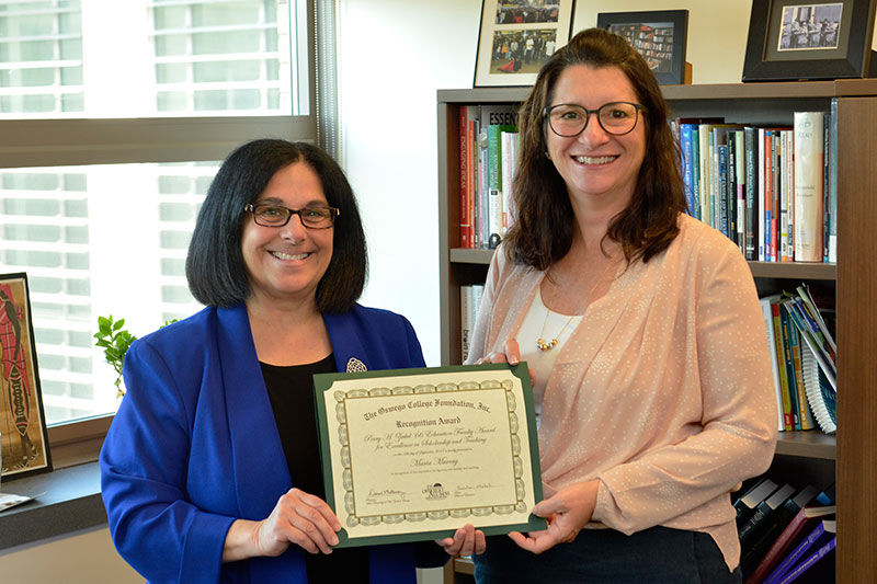 Maria Murray and School of Education Dean Pam Michel display Murray's Perry A. Zirkel Award for teaching