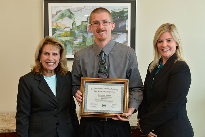 President Deborah F. Stanley and Graduate Studies Dean Kristen Eichhorn recognize graduate student Christopher Bartlett
