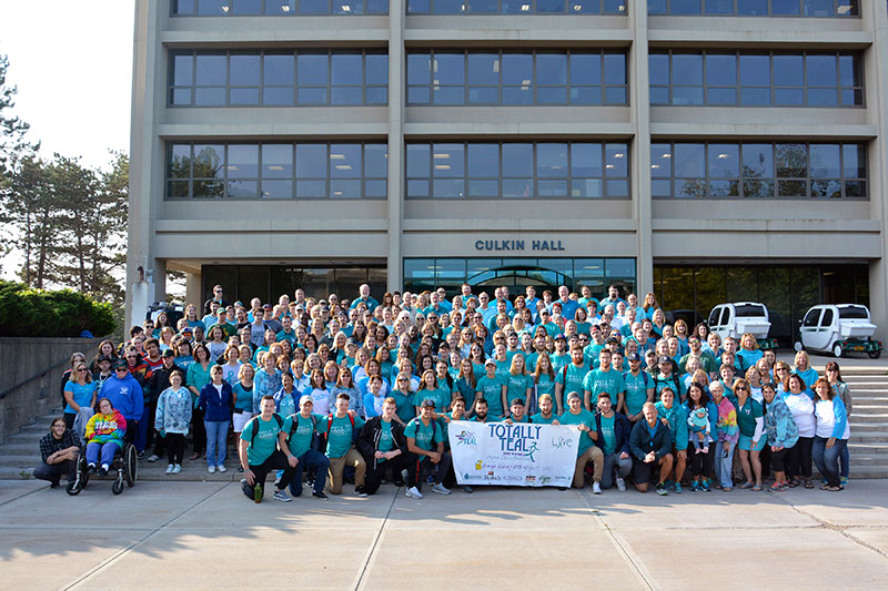 Campus community takes group photo in teal