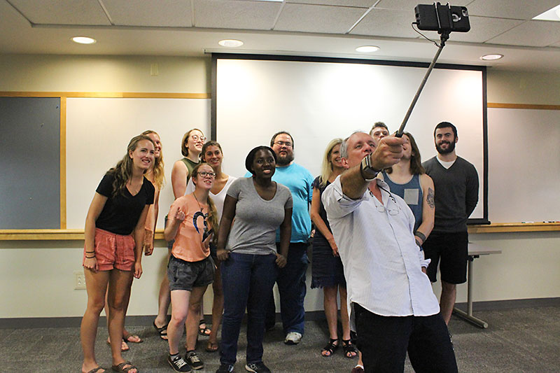 Paul Austin uses selfie stick to take photo with students