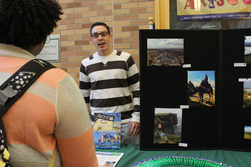 Student Tom Hardman speaks with visitors at Study Abroad Fair