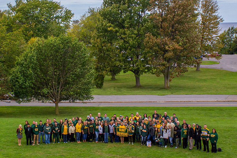 Members of the campus community pose in green and gold