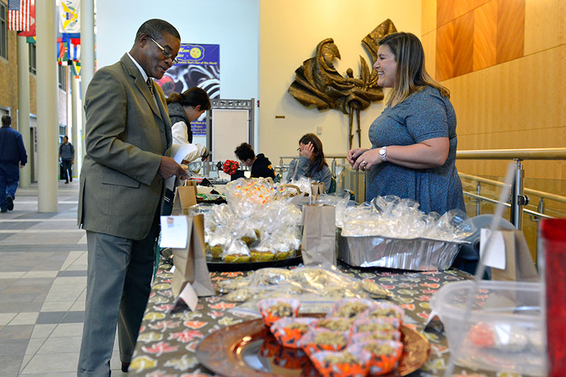 Howard Gordon buys desserts from Shelly Sloan at a table full of goodies