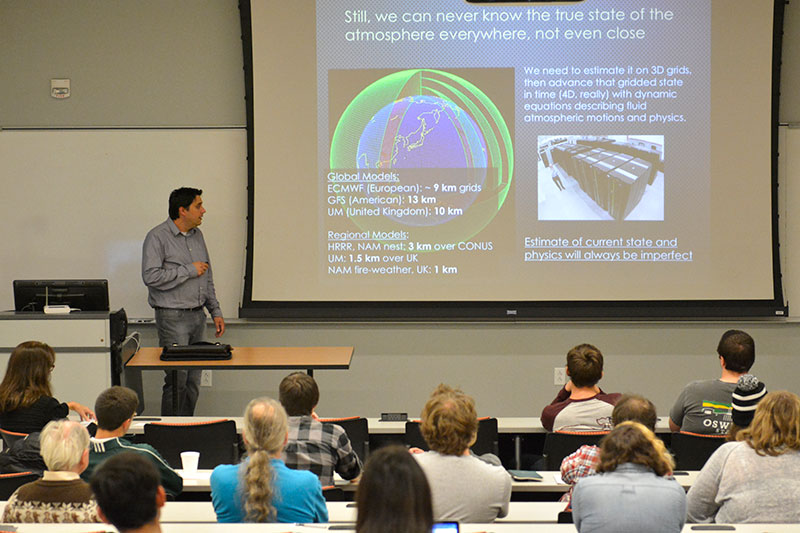 Alumnus Michael Coniglio, class of 1997 and research meteorologist for the National Severe Storm Labs, shares a projected slide about earth's atmosphere