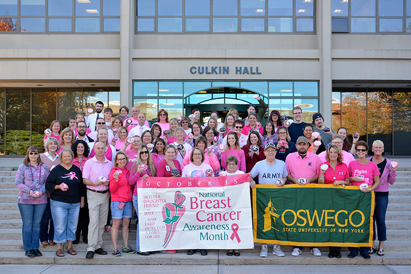 Crowd of campus members in pink, holding banners for National Breast Cancer Awareness Month and SUNY Oswego logo
