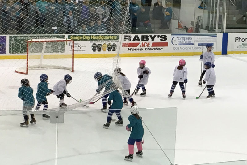 Oswego youth players vie for the puck during a between-periods mini-game