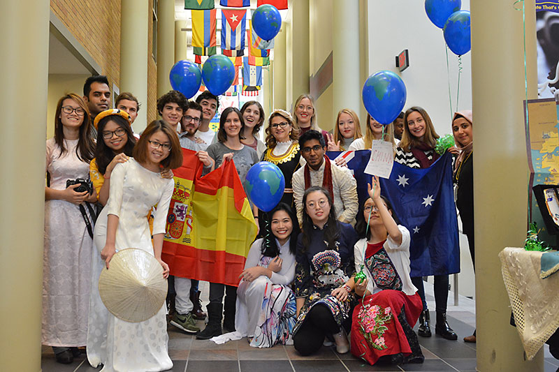 Group photo of international students, many dressed in clothes representing their culture