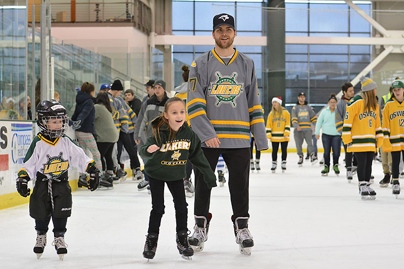 Laker hockey players skate with young fans