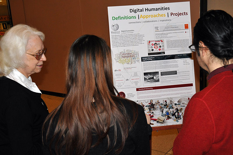 Faculty read posters at College of Liberal Arts and Sciences interdisciplinary collaboration event