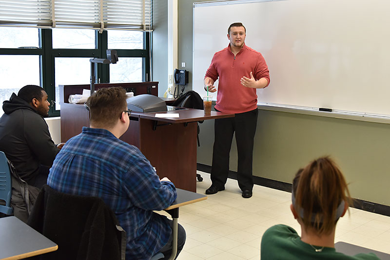 Tucker Sholtes, an alumnus now an advisory associate at PwC/PricewaterhouseCoopers, speaks with communications class