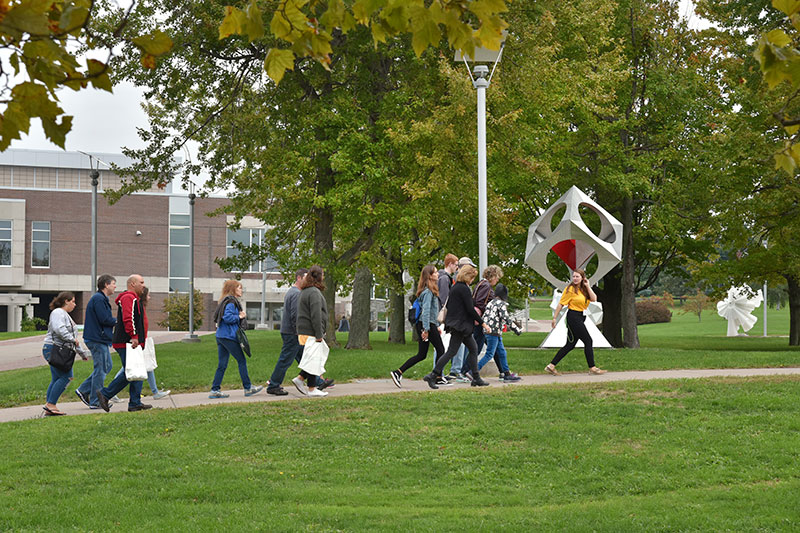 Tour guide leads visitors across campus