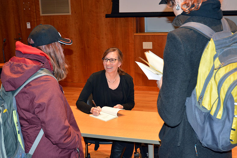 Poet Rebecca Dunham signs copies of her Cold Pastoral collection for audience members