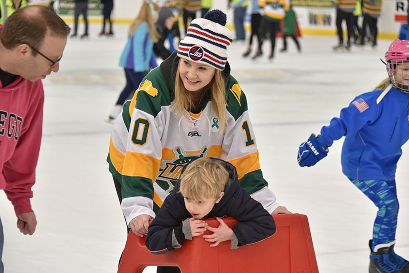 Women's hockey player Eryn Stewart helps a young skater