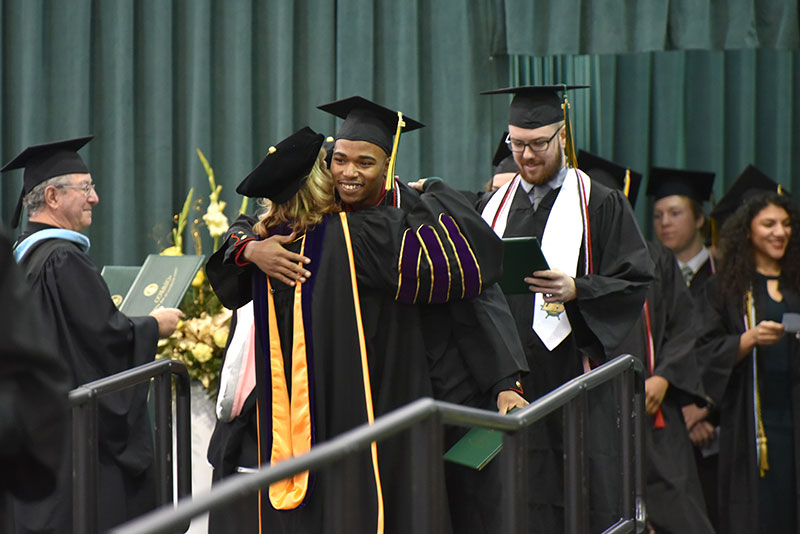Lamont Sadler hugs college President Deborah F. Stanley during the presentation of diploma