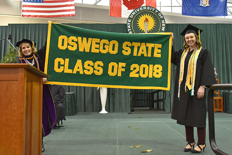 Alumni banner presenter Katherine Knopp (right) joins President Deborah F. Stanley hold up Class of 2018 banner