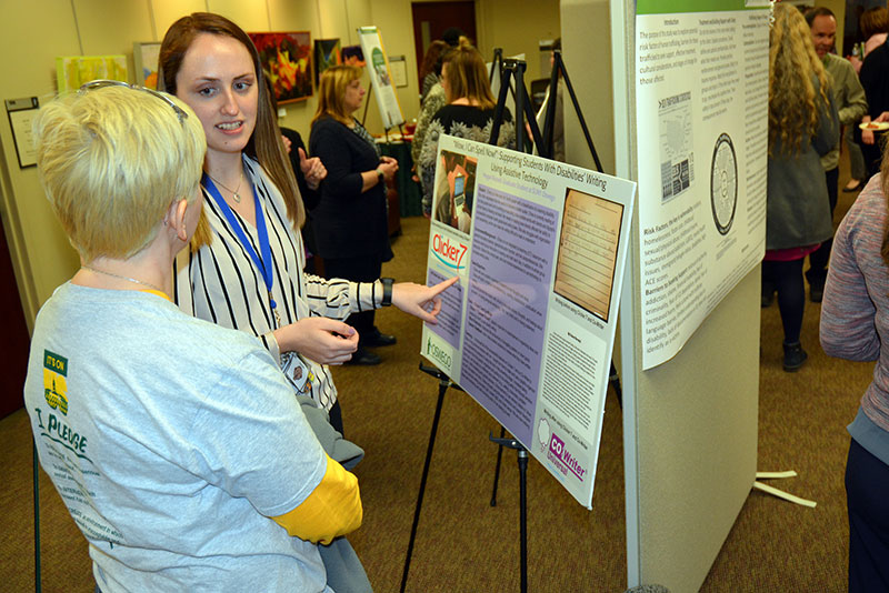 Graduate student Megan Russell explains her research on assistive technologies in the classroom to Mary Toale