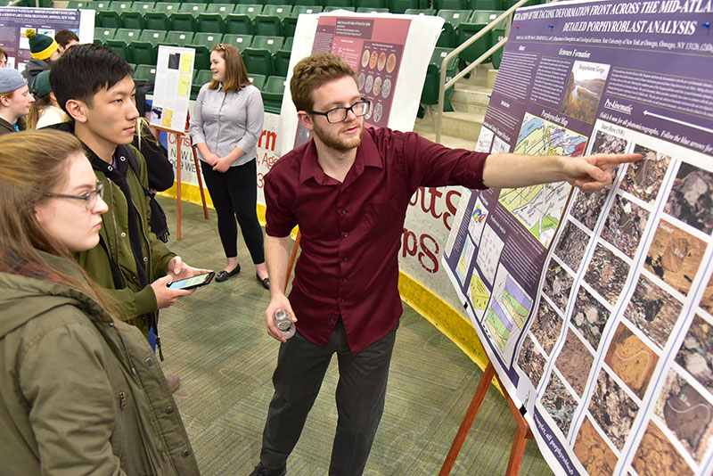 Geology major Christopher Weiman explains his research at Quest's Poster Session