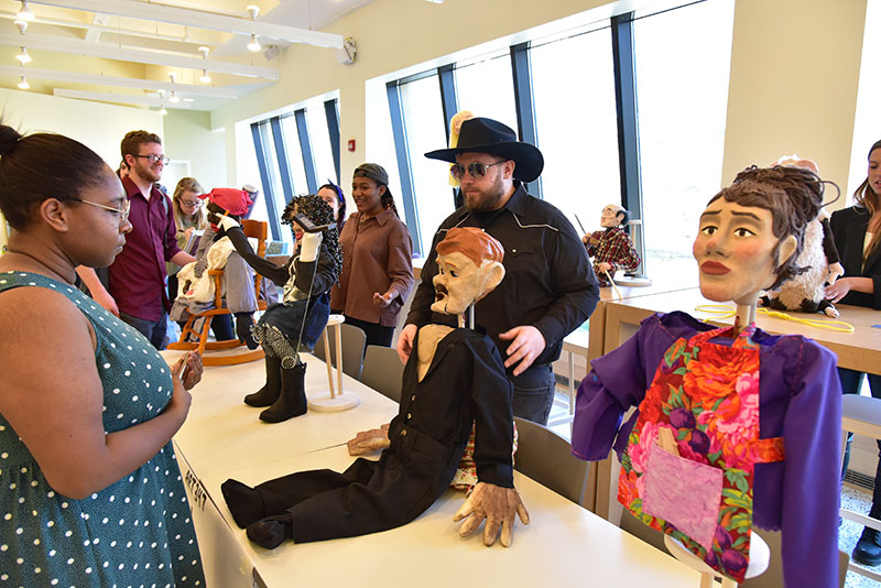 Studio art major Nate Canfield displays the puppets he sculpted