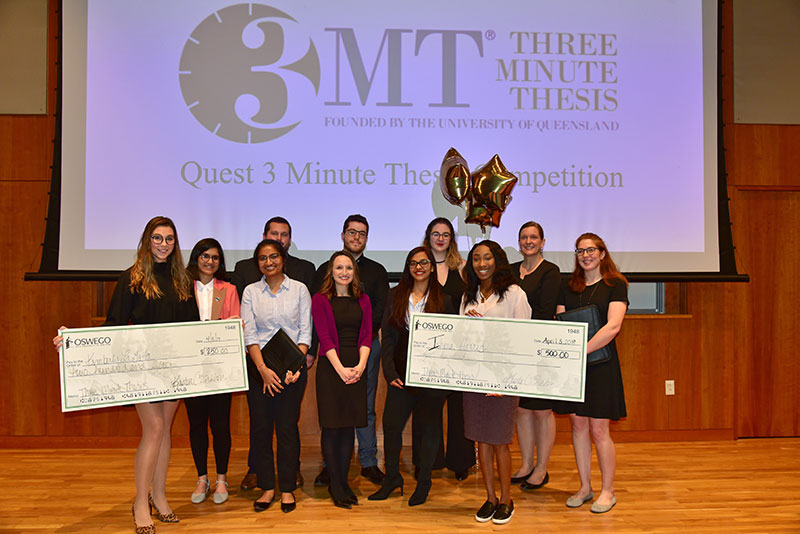 Students in Quest's 3-Minute Thesis competition gather, including two prize winners with their oversize checks