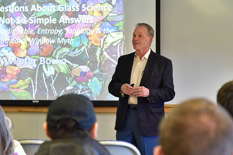 Alumnus Peter Bocko speaks with a class about glass science