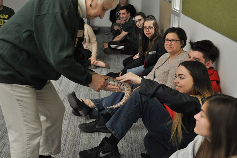 Zoo volunteer lets Focus Forward students touch a live skink