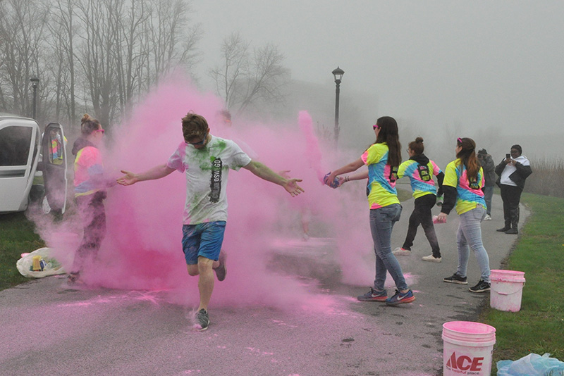 A runner gets sprayed with pink powder as they finish Color Oswego