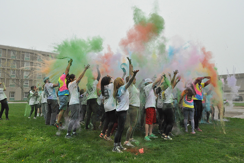 A powdery rainbow soars over Color Oswego participants and volunteers