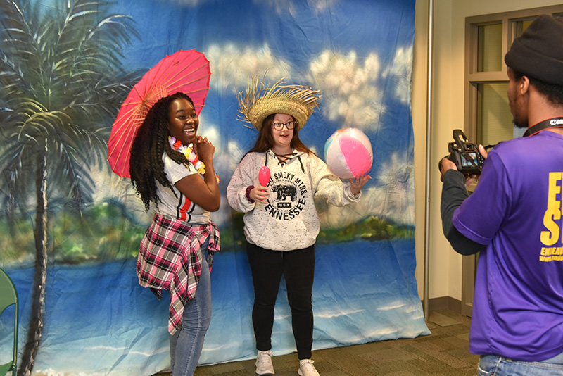 Students Shyanne Reid (left) and Ashley Savage have their photo taken in tropical style at OzFest's photo booth