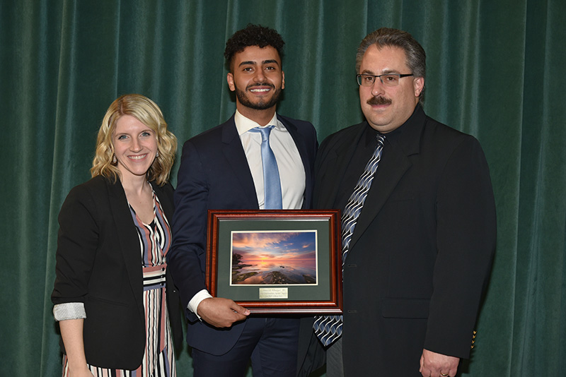Ahmed Albajari with staff celebrating his selection as 2019 Outstanding Senior