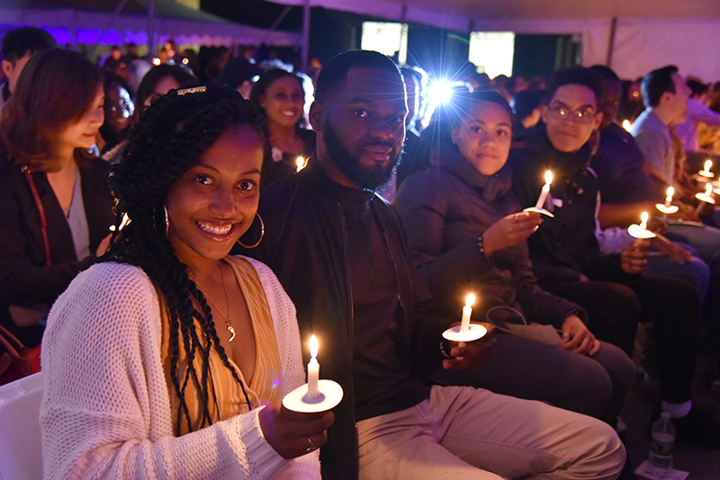 Skye Prosper (foreground), displays the Torch of Learning, a flame passed among her fellow graduating seniors at the Torchlight Ceremony