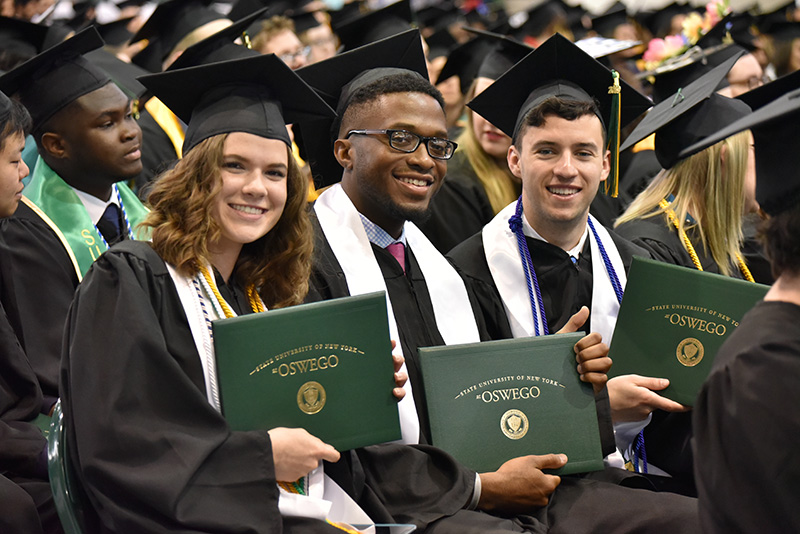 New graduates (from left) Rachel Meyer, Akim Cadet and Colin Maggiolo celebrate after the the 9 a.m. Commencement ceremony