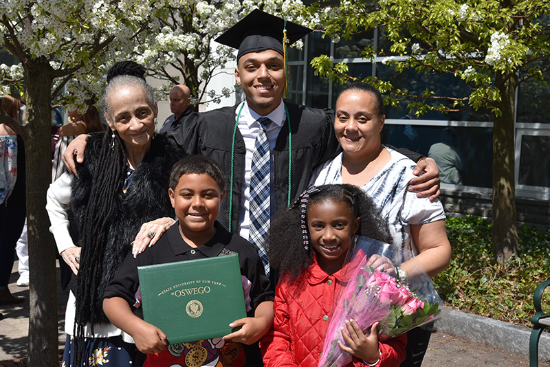 Family members gather around mathematics major Darryl Gomez-Lewis to celebrate his big day following Commencement
