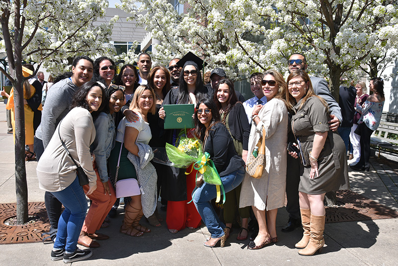 Human development major Desiree Pedrosa (center, in cap and gown) enjoys considerable support for her graduation achievement