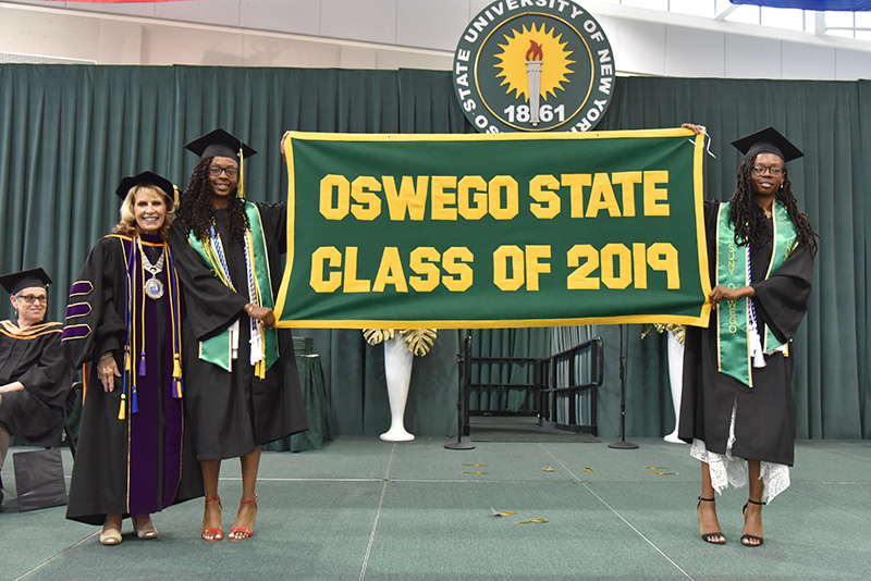 Campbell twins with President Deborah F. Stanley and Class of 2019 banner