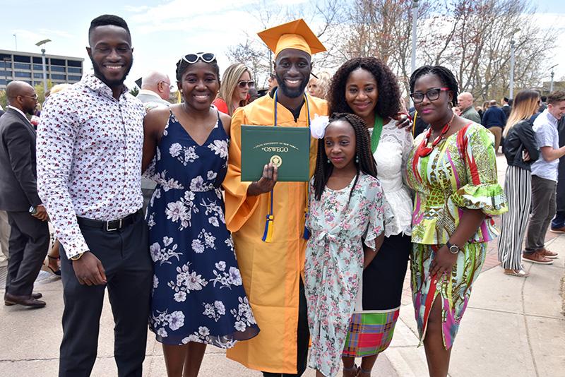 Family members surround finance major and economics minor Dillon Nimako following Commencemen