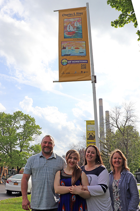 Gianna Ellingwood (second from left), a sixth-grader at Charles E. Riley Elementary School, celebrates her art's inclusion in the My Hometown Banner project with her parents and teacher