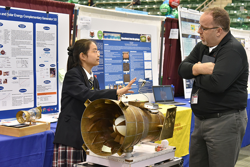 Fengyun Chen, a student from China, explains her project using wind force pressurization with complementary solar energy to generate electricity