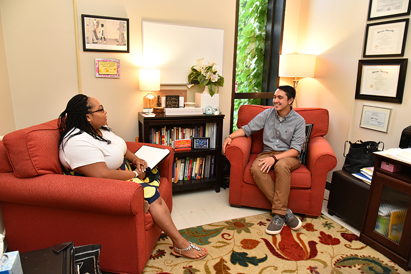 Cara Plasencia (left), of the Counseling Services Center, talks in her new office with colleague Kyle R. Dzintars