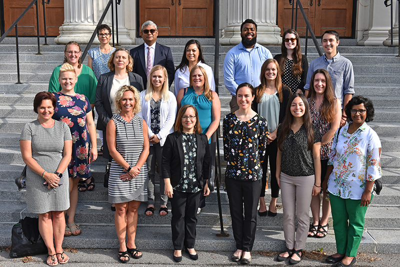 New professional staff pose on the steps of Sheldon Hall
