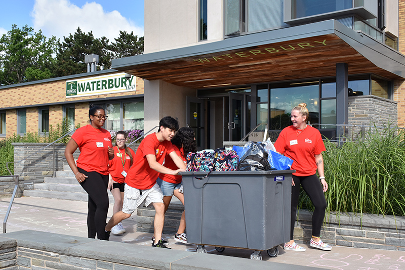Emma Semmler (right) leads her fellow crew members with a cart full of belongings into Waterbury Hall