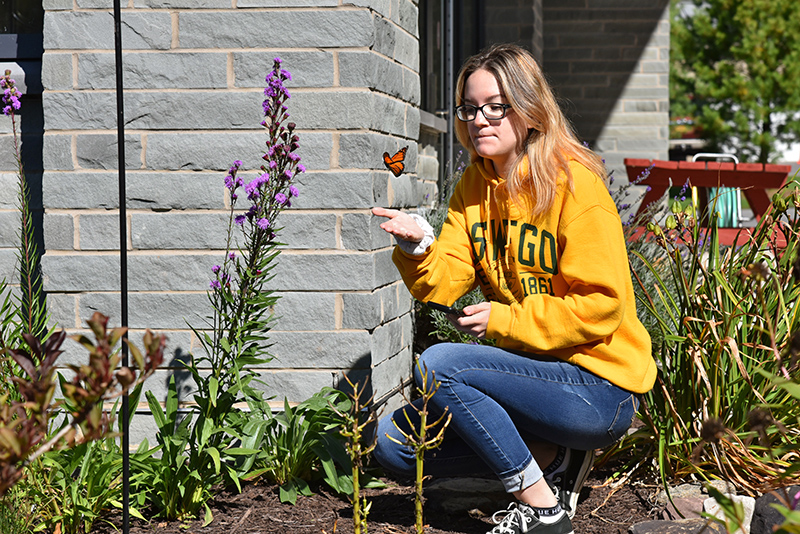 Elena Jones, a junior zoology major from the Bronx, waits to see if a butterfly will settle on her