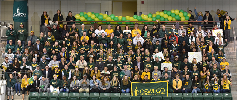 Campus community members in a large group wearing green and gold