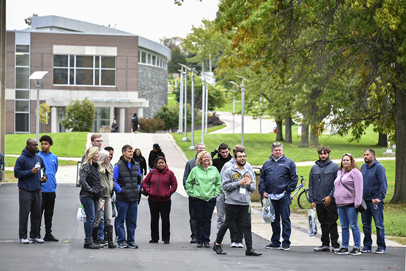 Nathan DeSantis, an adolescence education and Spanish major, leads a tour outside Penfield Library during the college's first Admissions Open House of the season