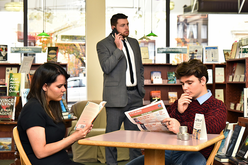 Production image in a bookstore for Dead Man's Cell Phone student honors theatre production