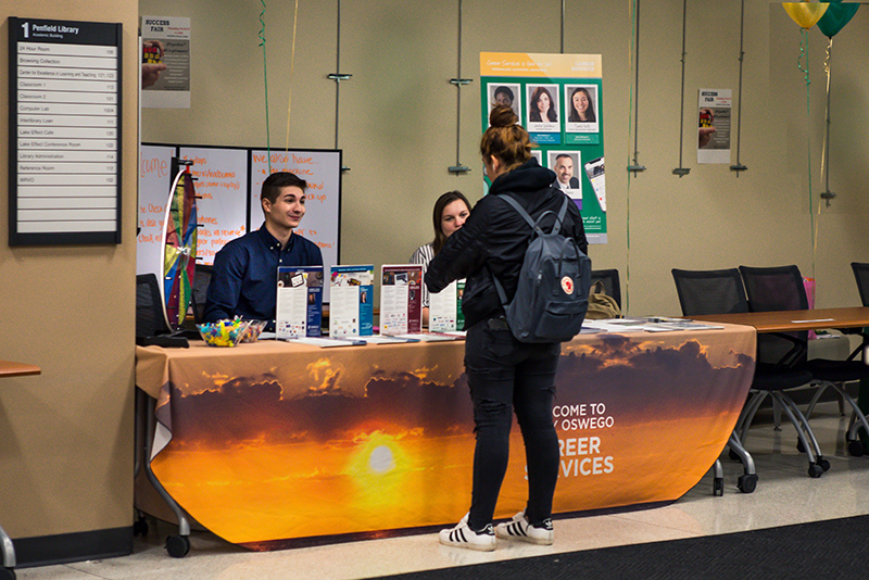 Justin McKissick and Emily Ziemba, representing Career Services, talk with students Oct 24 in the lobby during Penfield Library's hosted Success Fair