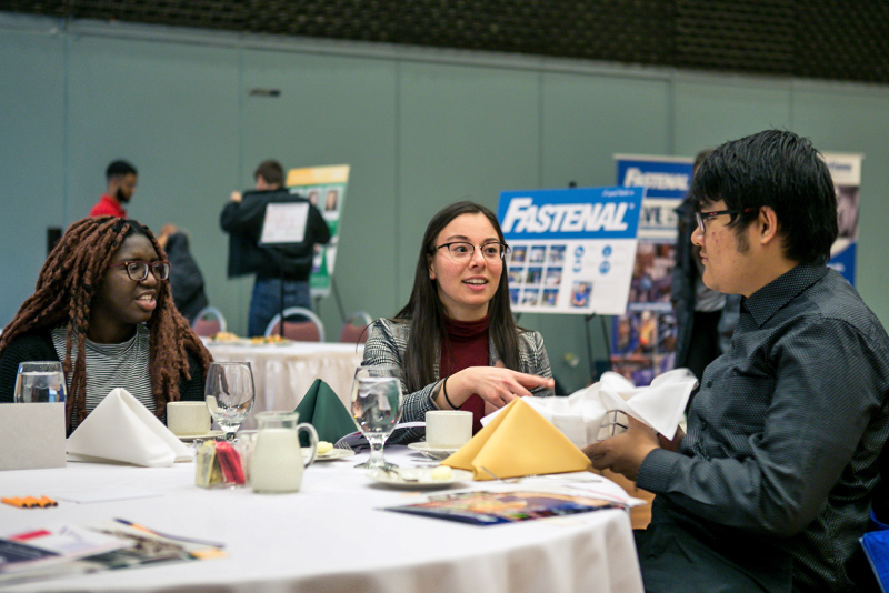 Taeko Kelly of the Career Services Office makes conversation with students Alikeju Adejo (left) and Phone Paing at the Fall Etiquette Dinner