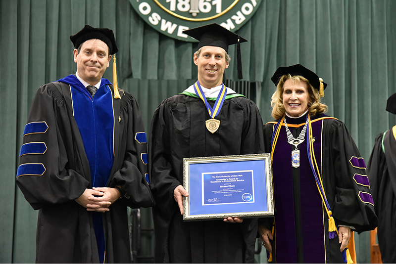 Richard Buck (center), director of digital services in the Office of Communications and Marketing, for receives a 2019 SUNY Chancellor's Award for Excellence in Professional Service