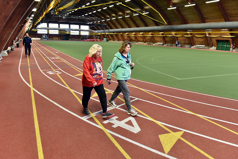 Oswego residents Daine Chesare, foreground left, Sally Clarke and other community members took advantage of the indoor track at Romney Field House during Cruisin' the Campus