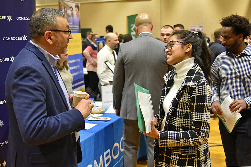 Ekta Siwakoti, a junior computer science and cognitive science dual major, talks during the March 4 Career and Internship Fair in Swetman Gymnasium with 1989 Oswego alumnus Phil Grome from OCM BOCES in Syracuse